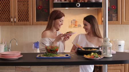 lesbijki : Two young beautiful girls prepare a vegetable salad in the kitchen, have fun talking and laughing. Two sisters prepare a salad of tomatoes and cucumbers in the kitchen in the morning.