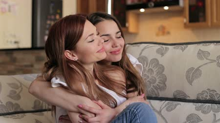 leszbikus : Two cute happy girls sitting hugging on the couch, they closed their eyes with pleasure. Stock mozgókép