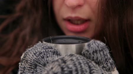 knitted gloves : Close-up of the face of a girl who drinks hot tea in the winter on the street, she wears knitted mittens. A girl drinks coffee in the winter in the park, from the mug there is steam.