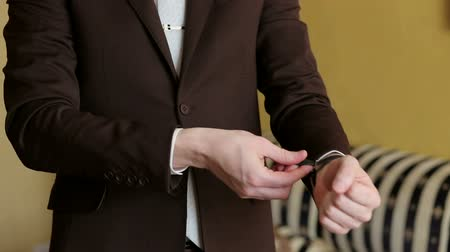 sleeve : Close-up of a man in a brown suit fastens the watch on his hand. Stock Footage