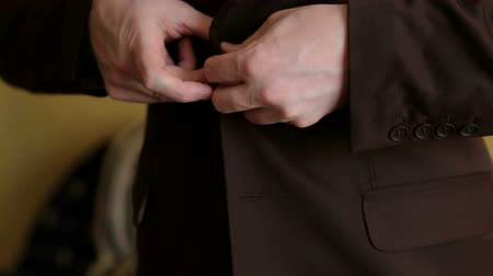 mandzsetta : Successful businessman buttoning a button on his brown jacket, close-up.