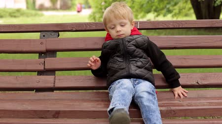znuděný : Close-up of a sad little boy of five years in a black jacket sitting on a bench in a park, the background is blurred.