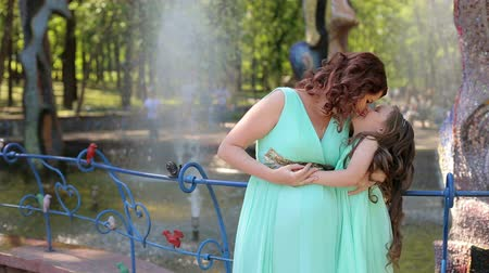 одиноко : A pregnant woman and her little daughter are standing near the fountain in identical dresses.