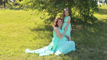 identical : Portrait of a cute pregnant woman and a little girl in the Park on the grass in Sunny warm windy weather, they are dressed in the same turquoise dress. Stock Footage