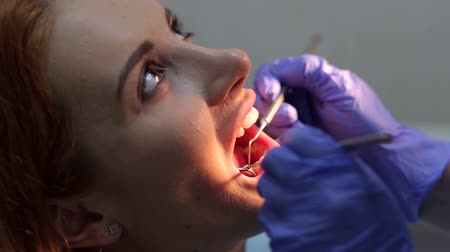 лечение зубов : Close-up face of patient with illuminated open mouth and hands of dentist with dental instruments.