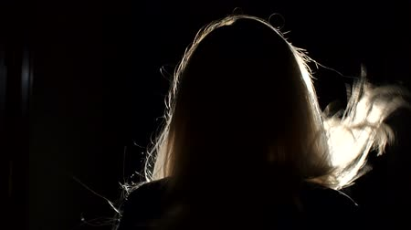 tmavé vlasy : Silhouette of a woman with long blond flying hair that slowly walks through a long black corridor to the light. Dostupné videozáznamy