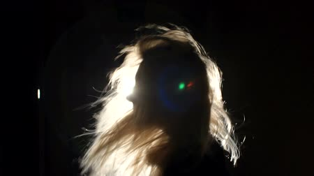 темно : Close-up silhouette of a girl with long blond hair in the dark. Luxurious girl Waving her head and her hair flies in different directions in the dark with the light of a bright lantern, slow motion.