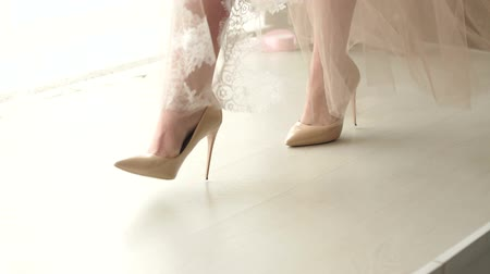 negligee : Close-up of a girl in high heels and a long translucent dress is on the catwalk, slow motion. Underwear. The bride in the negligee in the boudoir.