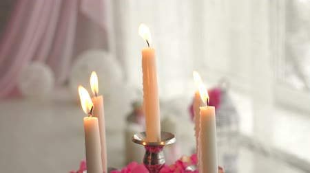 cera : Close-up of candlesticks with burning candles on a background of pink flowers and satin ribbons, slow motion.