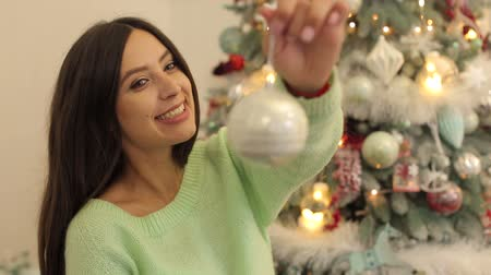 enfeite de natal : A happy girl in a warm sweater is holding a Christmas ball on the background of a decorated Christmas tree. Stock Footage