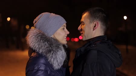 náklonnost : A loving couple is standing in an embrace in the winter evening in the park. Portrait of a couple in winter at night, they hug and kiss. Close-up.