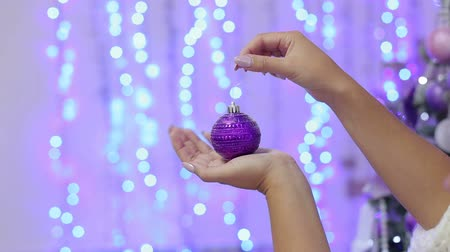 silvery : The girl is holding a purple Christmas ball in her hands against the background of blurred flashing lights. Close-up. New Year. Christmas. Bokeh. Background. Stock Footage
