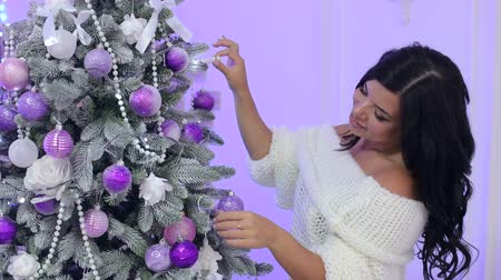 stockings : A beautiful girl in a warm knitted sweater decorates a Christmas tree. Beautiful Christmas interior.