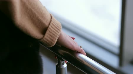 forefinger : Close-up of a girl in a warm sweater holding hands over a metal handrail.