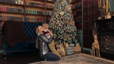 newyear : Happy mother and son hugging near the Christmas tree, a lot of boxes with gifts. Stock Footage