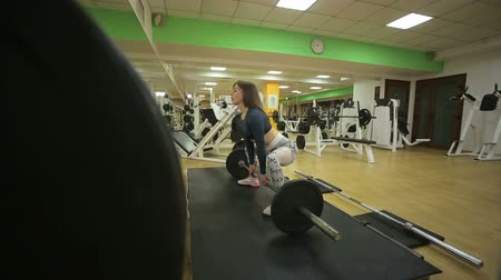 súlyzó : Bodybuilding. Strong fit woman exercising with barbell. Fitness woman preparing to practice deadlift with heavy weights in gym. Female doing heavy weight lifting workout in health club.
