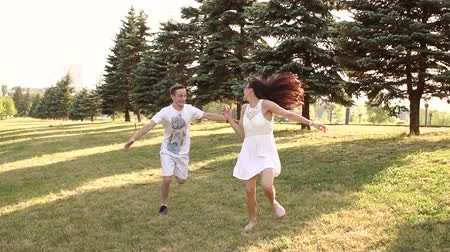 run down : Happy young couple running on the grass in the Park, guy trying to catch his girlfriend. Slow motion.
