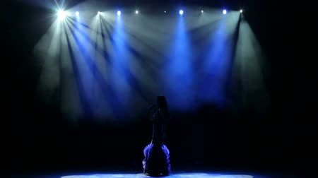 divas : Silhouette of a luxurious singer in an evening gown on a stage in the dark. The girl sings a song on an empty stage in the light of a blue spotlight.