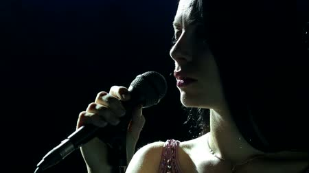 cantora : Silhouette of a beautiful girl singer with microphone in the dark. Vídeos