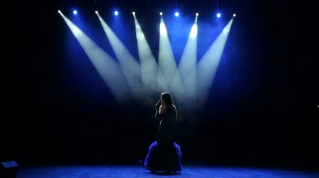 músico : A young woman in a luxurious evening dress sings a song and dances on a dark smoky stage. Stock Footage