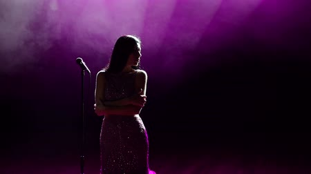 divas : Young beautiful singer sings on stage in the light white and pink spotlights.
