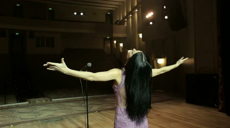 capa dura : Close-up portrait of a beautiful singer with a microphone, she put her hands to the side. Young woman singing in microphone on an empty stage, close-up. The view from the back.