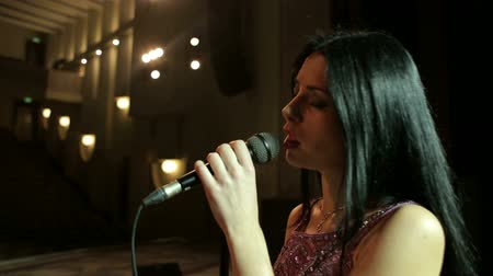 capa dura : Close-up portrait of a beautiful singer with a microphone. Young woman singing in microphone on an empty stage, close-up.
