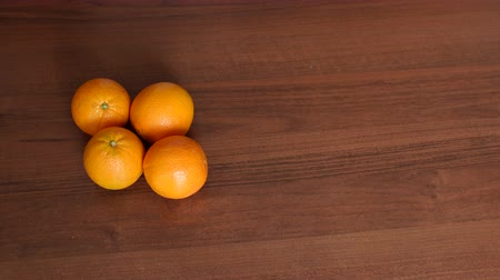 nedvdús : Four ripe juicy oranges on a brown wooden surface. Close-up. High resolution.