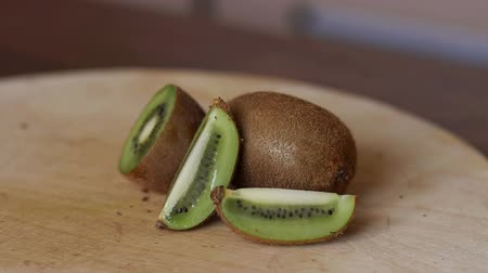 kivi : Close-up of ripe sliced kiwi on wooden background. Ripe sliced kiwi on cutting Board, Slow motion.
