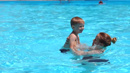 két ember : A cheerful family, a young mother with her son, have fun and play in the pool. They bathe, sunbathe and enjoy the hot weather in the hotel at the resort. Stock mozgókép