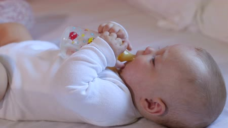 infant formula : A newborn baby is lying on the bed and drinking water or milk from the bottle. Close-up. Newborn boy eating close-up.