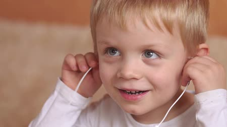 ouvir : Close-up of the face of the little emotional boy with headphones. The child first listens to music with headphones. Portrait of happy boy with headphones in the bedroom