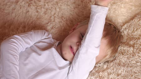 acorde : Portrait of a cute little boy who wakes up in the morning in bed and covers her face with hand. Close-up of a small child in the morning in bed on a fluffy soft blanket. Stock Footage