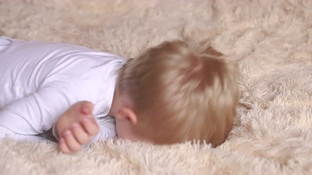 ložnice : A cheerful little kid is played on the bed on a soft fluffy blanket. A happy little boy wakes up in the morning in bed Dostupné videozáznamy
