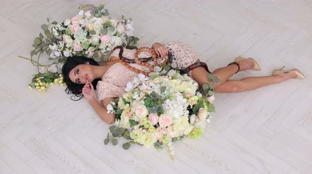 womanhood : A sexy girl lies on the floor among large bouquets of flowers and two snakes creep along it. Beautiful girl holds a snake in hands on a white background. Wide shot. Stock Footage