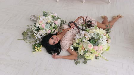 womanhood : A sexy girl lies on the floor among large bouquets of flowers and two snakes creep along it. Beautiful girl holds a snake in hands on a white background.