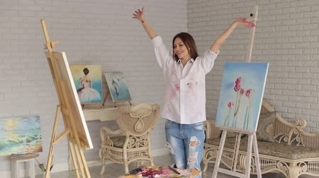 realization : A happy creative girl artist in a white shirt and jeans in a studio among many paintings. Young artist painting in the house. Art. Stock Footage