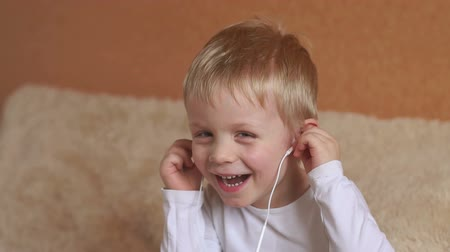 ouvir : Emotional happy surprised boy with headphones first listening to music in the bedroom on the bed, children, technology and people concept.