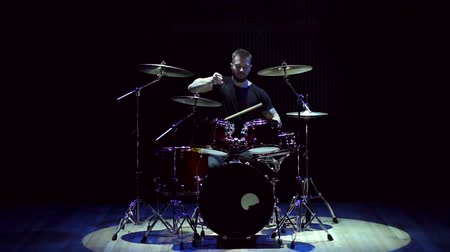 concert hall : A young musician drummer plays on stage on a drum set on a black background with the light of a blue and white spotlight.