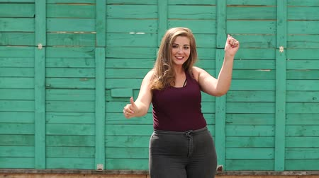 xxl : Young beautiful girl with overweight in summer park showing thumbs up on green wooden wall background. Plus size. Slow motion.