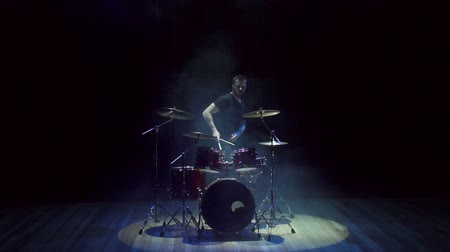 throws : A male drummer plays a drum set on stage in the dark, he finishes the performance gets up and leaves the stage. Slow motion.