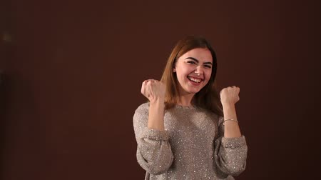 victorious : Portrait of a successful woman in the Studio on a brown background, she screams and raises his hands up. Slow motion.