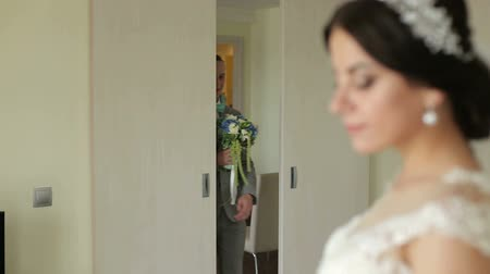 gives : The happy groom opens the door and enters the brides room with a bouquet of flowers. The bride in the foreground is blurred. Stock Footage