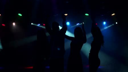 floodlight : A group of teenagers dancing at the concert in the dark with smoke and lighting equipment. Silhouettes of dancing people having a celebration in a disco club. Slow motion.