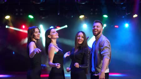повод : Young cheerful company of friends dancing and having fun at night at a party, slow motion. Disco lighting with multi-colored spotlights.