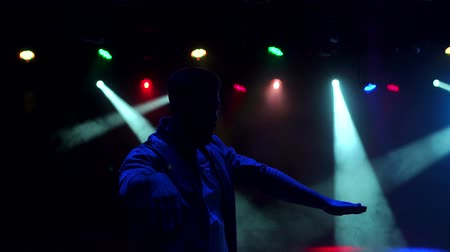 félrebeszél : Silhouette of a cheerful young guy dancing in the dark in a nightclub, slow motion.