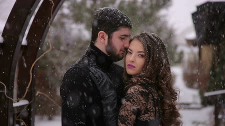 dead forest : The bride in a black dress is embracing with the groom in a heavy snowfall in a wooden arch. Wedding. Bride in a black dress. Gothic wedding.