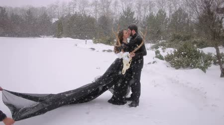 wampiry : The bride in a black dress with a long black veil fluttering in the wind. A pair dressed in a Gothic style stands on the snow with a large skull in their hands. Gothic wedding.