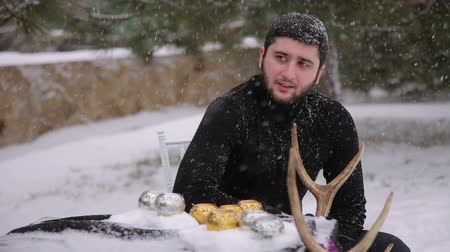 vampiro : A brutal man with a beard sitting at a table outdoors in heavy snow, the table is decorated with black cloth, skull and candles. Gothic wedding.