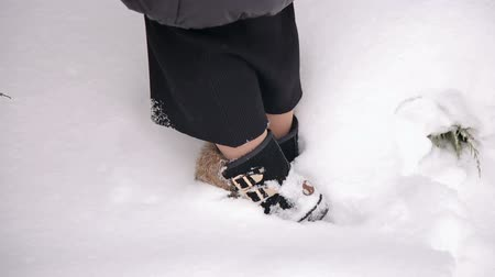 goes : Close-up of a girl in winter fur boots with metal clasps standing in the snow in winter. Stock Footage
